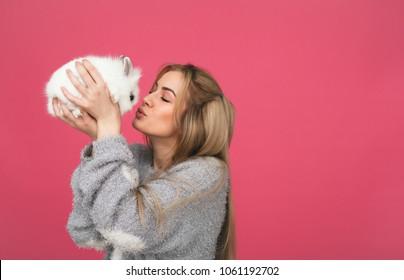 Lächelnde junge Frau, die weißes Kaninchen küsst. rosafarbener Hintergrund.