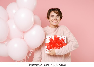 Smiling young woman in knitted casual sweater holding red present box with gift ribbon bow, bunch of air balloons celebrating birthday holiday party isolated on pastel pink background studio portrait