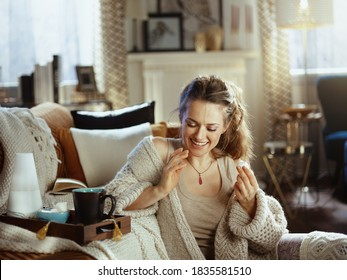smiling young woman in knitted cosy cardigan with tray, aroma lamp, mug and pastries eating pastries at modern home in sunny autumn day.