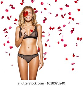 A smiling young woman in lace black lingerie stands with candy on a stick in the shape of a red heart and looks through the candy. Girl stands against the background of falling rose petals on Valentin