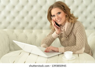 Smiling young woman with laptop and smartphone
