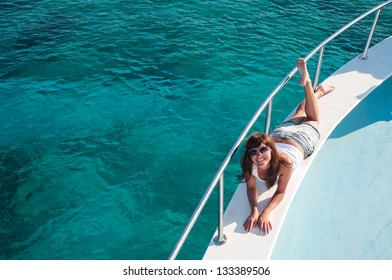 Smiling young woman laying on yacht deck. Copyspace