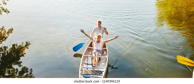 Smiling young woman leaning back on her boyfriend and enjoying nature and fresh air while canoeing on a lake