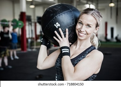 Smiling Young Woman Lifting Medicine Ball