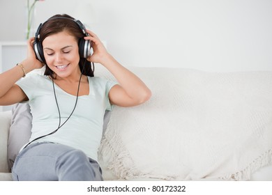 Smiling young woman listening to music sitting on a sofa