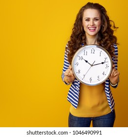 smiling young woman with long wavy brunette hair against yellow background showing clock