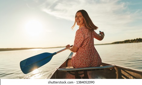 Smiling young woman looking back over her shoulder while paddling a canoe on a lake on a sunny summer afternoon