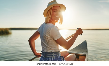 Smiling young woman looking back over her shoulder while paddling a canoe on a still lake on a summer afternoon