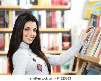 smiling young woman looking for a book in a bookstore -  looking at camera