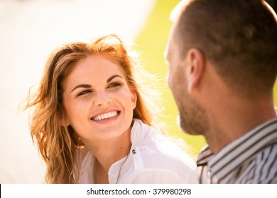 Smiling young woman looking to eyes of her man on date outdoors