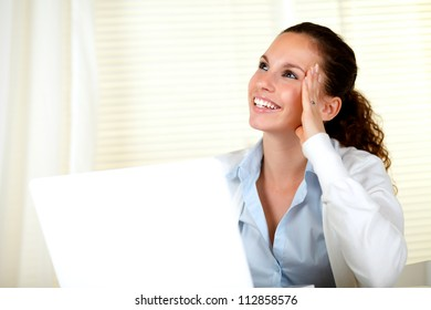 Smiling young woman looking up in front of her laptop - copyspace