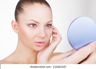 Smiling young woman looking in the mirror on a light background