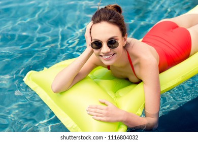 smiling young woman lying on inflatable mattress in swimming pool