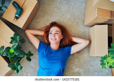Smiling young woman lying on floor in new apartment and looking away