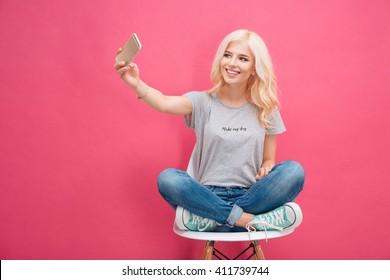 Smiling young woman making selfie photo on smartphone over pink background