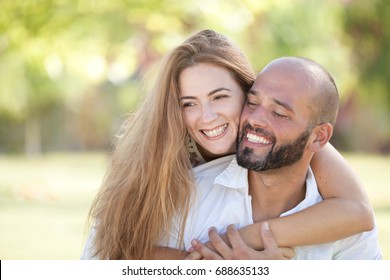 Smiling Young Woman and Young Man are Happy Together - they are Smiling and Embracing in Nature at the Bright Sunny Day