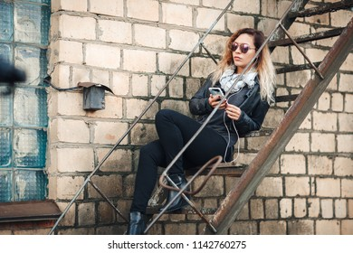Smiling young woman in mirrored sunglasses, a black leather jacket, black jeans sitting on an urban metal stair against a brick wall. Woman listening to music on the stairs of industrial building.