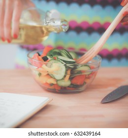 Smiling young woman mixing fresh salad in kitchen