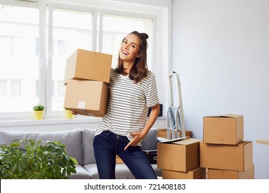 Smiling young woman moving to new apartment, holding boxes and looking at camera
