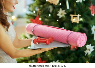 smiling young woman near Christmas tree holding fitness gear