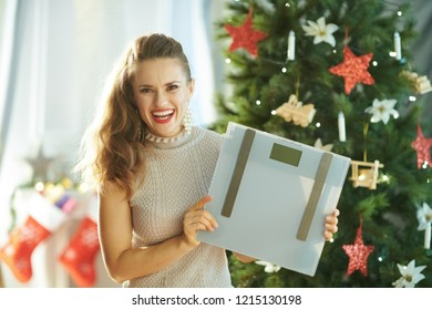 smiling young woman near Christmas tree showing weight scales