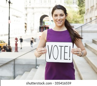 A smiling young woman on building steps wit a 'VOTE' sign.