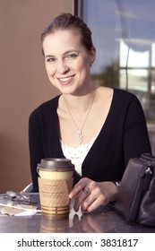 A smiling young woman on cafe patio enjoying a coffee or tea.