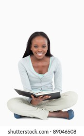 Smiling young woman on the floor with her book against a white background