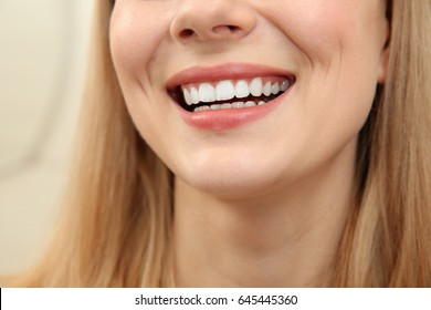 Smiling young woman on light background, close up
