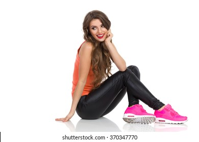 Smiling young woman in orange shirt, black leather trousers, pink sneakers sitting on a floor and looking back over the shoulder. Side view. Full length studio shot isolated on white.