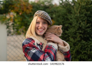 Smiling young woman with ore cat on natural background. Cozy autumn. Hugge soft concept