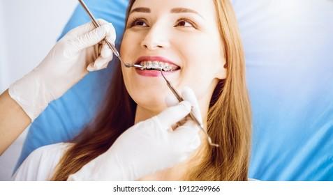 Lächelnde junge Frau mit kieferorthopädischen Klammern, die vom Zahnarzt in der sonnigen Zahnklinik untersucht wurde. Konzept für gesunde Zähne und Medizin