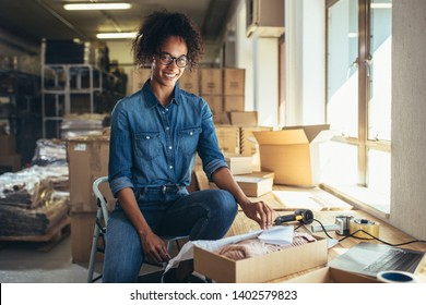 Smiling young woman packing the product in a box for shipping to the customer. Online business owner working at the office.
