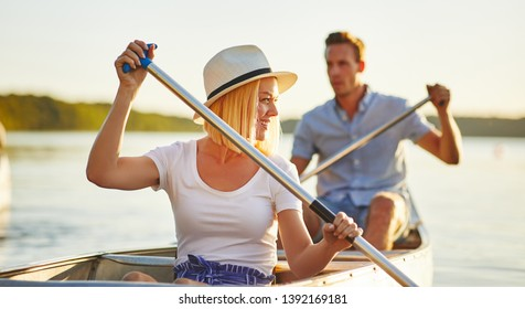 Smiling young woman paddling a canoe with her boyfriend on a lake on a sunny summer day