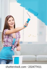 Smiling young woman painting the walls in her apartment with blue color paint
