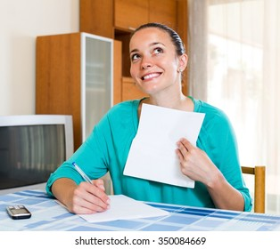 Smiling young woman with papers at the table at home