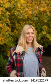 Smiling young woman in park. Trees with yellow leaves. Cozy autumn. Hugge soft concept