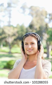 Smiling young woman in the park wearing headphones