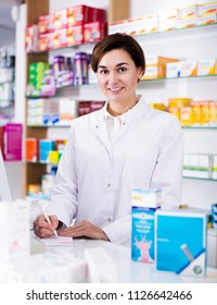 Smiling young woman pharmacist ready to assist in choosing at counter in pharmacy