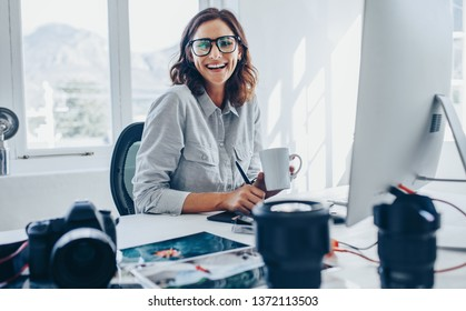 Smiling young woman photo editor with cup of coffee sitting at her desk. Female photographer in her office.