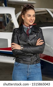 Smiling Young Woman Pilot Portrait. Portrait of beautiful young woman pilot standing in front of private plane. Female pilot with modern small aircraft in background.
