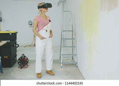 Smiling young woman in pink shirt and white overalls standing relaxed at workplace at half-painted yellow wall with hands in pockets in virtual reality goggles headset.