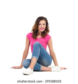 Smiling young woman in pink shirt and jeans sitting on the floor. Full length studio shot isolated on white.