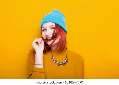 Smiling young woman playing with her red hair on yellow background