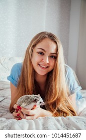 Smiling young woman playing with a little hedgehog in the bedroom
