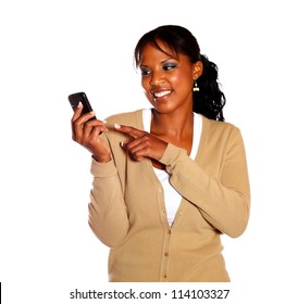 Smiling young woman pointing her cellphone on isolated background