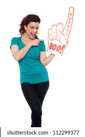 Smiling young woman pointing at large foam hand isolated against white background