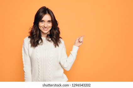 Smiling young woman points a finger away isolated on orange background