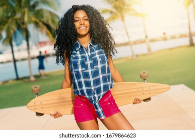 Smiling young woman portrait holding long board in South Pointe Park. Natural flare. Life style. South Beach Miami, Florida.