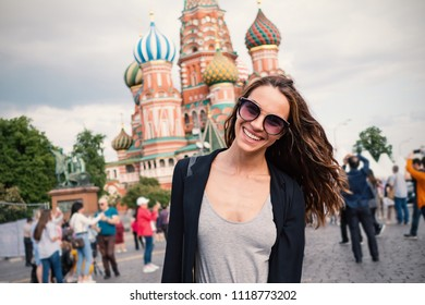Smiling young woman portrait in Red Square, with Saint Basil's Cathedral in the background. Moscow, Russia.